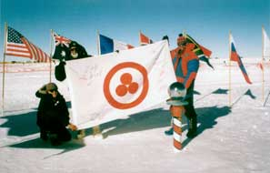 "V. Chukov (Russia), V. Drabo (Belarus), and worker of the American Pole Station ""Amundsen-Scott"" with the Banner of Peace on the South Pole. January 8, 2000."